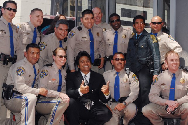 Actor Erik Estrada (C) best known for his role as Officer Frank Ponch Poncherello in the 1977-1983 television series CHiPS, poses with California Highway Patrol officers with his star on the Hollywood Walk of Fame in Los Angeles on April 19, 2007. Estrada has now become a reserve police officer in Idaho. File Photo by Jim Ruymen/UPI