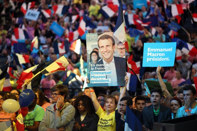 Supporters cheer centrist candidate for the 2017 French presidential election Emmanuel Macron during a campaign rally in Paris on April 17, 2017. Overseas voters began to cast their ballots in various French territories on Saturday ahead of the mainland votes on Sunday. 
