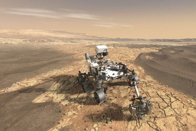 In an artist's conception, the Mars 2020 rover is seen introducing a drill that can collect core samples of the most promising rocks and soils and set them aside on the surface of Mars. A future mission could potentially return these samples to Earth. File Photo by NASA/UPI