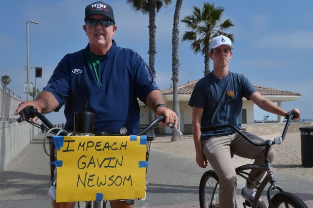 A man expresses his displeasure with California Gov. Gavin Newsom as he rides his bike in Huntington Beach in April of 2020 after the Democratic governor ordered a temporary hard close only of beaches in Orange County amid the pandemic. On Wednesday, it was confirmed that Newsom will face a recall election. Photo by Jim Ruymen/UPI