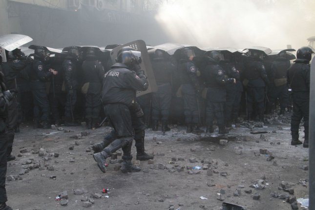 Ukrainian riot police officers shelter themselves from stones during a clash with anti-government protesters outside the parliament building in Kiev on February 18, 2014. UPI/Sergey Starostenko