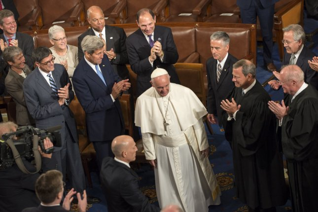 Pope Francis enters past Secretary of State John Kerry and Supreme Court Chief Justice John Roberts as the Pope enters to become the first Pope to address a joint meeting of Congress in the House Chamber at the U.S. Capitol in Washington, DC on September 24, 2015. The Pope is on his first trip to the United States, and also visits New York and Philadelphia. Photo by Pat Benic/UPI