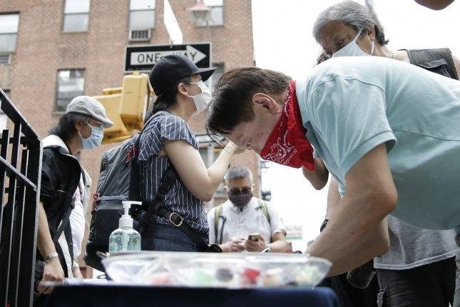 Members of Concerned AsAm Citizens of NYC greet people on the street and ask them to take part in the Asians Are Not A Virus 2020 campaign in the Chinatown section of New York City on Saturday. Photo by John Angelillo/UPI