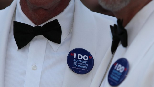 A gay couple sports buttons supporting same-sex marriage. (UPI Photo/David Silpa)