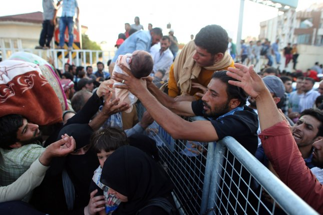 Syrians try to climb the fence while hundreds of refugees wait at the Syrian side of the border crossing in Akcakale, Sanliurfa province in southeast Turkey on June 14. They are trying to cross to the Turkish side as they are fleeing from the fighting between the Kurdish People's Protection Units (YPG) military group and Islamic State (ISIS). The State Department found a sharp rise in the number of terrorist attacks and people killed by terrorist worldwide in 2014. Photo by Ebrahem Khadir/ UPI
