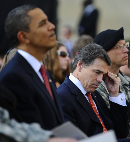 Texas Governor Rick Perry wipes his brow as he sits near U.S. President Barack Obama. Perry, though he hasn't made an official announcement, wants to run for the presidency. UPI/Tannen Maury/Pool