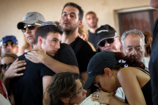 Family and friends mourn by the body of Ido Ben Ari, 42, during his funeral in Yavne, Israel, June 9, 2016. Ido Ben Ari died after being shot during a terror attack inside a restaurant in Tel Aviv on Wednesday night after two Palestinian terrorists opened fire killing four and wounding sixteen. Israeli security arrested the two Palestinian gunmen who were in Israel illegally from the West Bank. Photo UPI