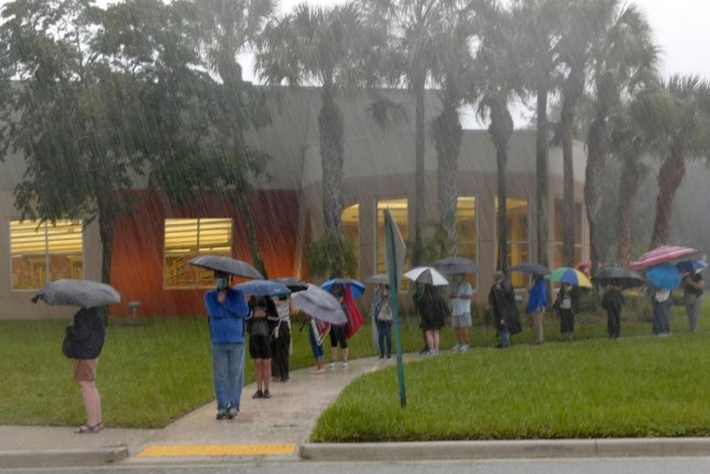 Residents in Palm Beach County wait in line in heavy rain Monday to cast their ballots early for the 2020 presidential election, at the Hagen Ranch Road Library in Delray Beach, Fla. Photo by Gary I Rothstein/UPI