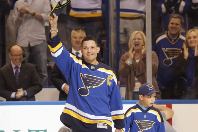 St. Louis Cardinals catcher Yadier Molina with son Yanuell wave to the crowd before participating in a ceremonial puck drop at the home opener between the St. Louis Blues and the Edmonton Oilers at the Scottrade Center in St. Louis on October 8, 2015. Photo by Bill Greenblatt/UPI