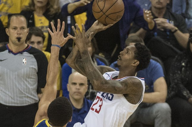 Los Angeles Clippers guard Lou Williams (23) puts up a shot over Golden State Warriors guard Stephen Curry (30) in the first quarter of Game 5 of the NBA playoffs on Wednesday night at Oracle Arena in Oakland, California. Photo by Terry Schmitt/UPI