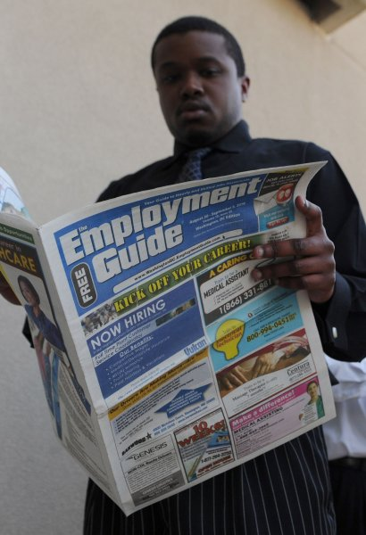 A job seeker reads an employment guide as he waits in line for the Metro DC Diversity Job Fair at FedEx Field in Landover, Maryland on August 31, 2010. UPI/Kevin Dietsch