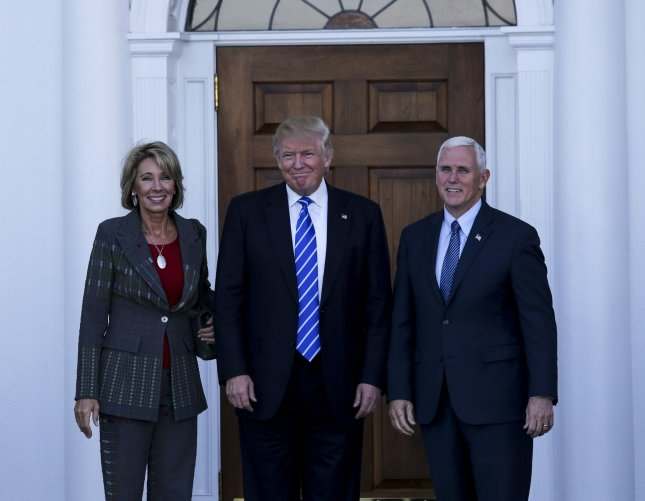 President-elect Donald Trump (C) and Vice President-elect Mike Pence (R) meet with Betsy DeVos at the clubhouse of Trump International Golf Club, November 19, in Bedminster Township, N.J. DeVos' confirmation hearing for secretary of education was postponed until January 17. Pool photo by Aude Guerrucc/UPI