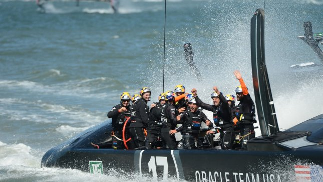 Oracle Team USA celebrates after winning the final race of the America's Cup Regatta against Emirates New Zealand (in distance) on San Francisco Bay on September 25, 2013. Oracle Team USA defeated challenger Emirates New Zealand 9-8 after being down 8-1 to retain the cup. UPI/Terry Schmitt