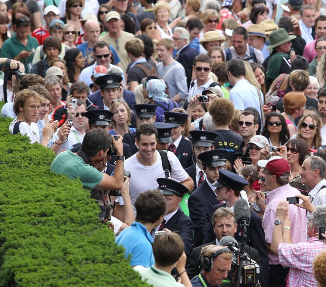 John Isner (L), flanked by security officers, walks through a large crowd at Wimbledon June 24, 2010, after outlasting Nicholas Mahut in the longest match in pro tennis history -- 183 games in 11 hours and 5 minutes. File Photo by Hugo Philpott/UPI