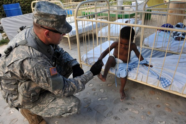 U.N. officials acknowledge for the first time the role peacekeepers played in a deadly cholera outbreak in Haiti. Pictured: Spc. John Emmerson with the Black Falcon Battalion of the 82nd Army Airborn shakes hands with a child at an outdoor children's hospital in Port-au-Prince, Haiti on January 26, 2010. File Photo by Kevin Dietsch/UPI