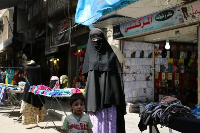 Vendors sell in the rebel-held Bustan al-Qasr district in eastern Aleppo, Syria on May 21. File Photo by Ameer Alhalbi/ UPI