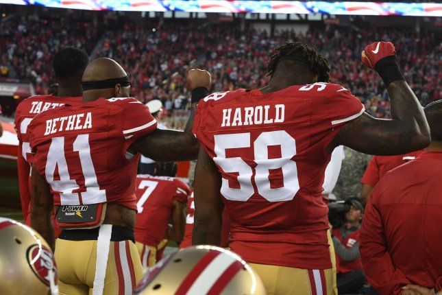 San Francisco 49ers players Antoine Bethea (41) and Eli Harold (58) hold up clenched fists as QB Colin Kaepernick (7) kneels during the National Anthem before playing the Los Angeles Rams in 2016 at Levi's Stadium in Santa Clara, Calif. Photo by Terry Schmitt/UPI