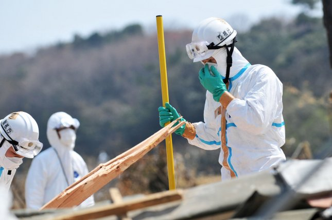 Japanese police, wearing chemical protection suits, search around the Fukushima Daichi Nuclear Power Plant in Minamisoma, Fukushima prefecture, Japan, on April 15, 2011 -- about a month after the disaster. File Photo by Keizo Mori/UPI