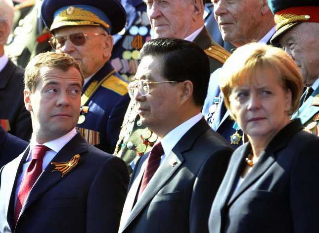 Russian President Dmitry Medvedev (L), Chinese President Hu Jintao and German Chancellor Angela Merkel (R) attend the Victory Day military parade marking the 65th anniversary of victory over Nazi Germany on Red Square in Moscow May 9, 2010. UPI