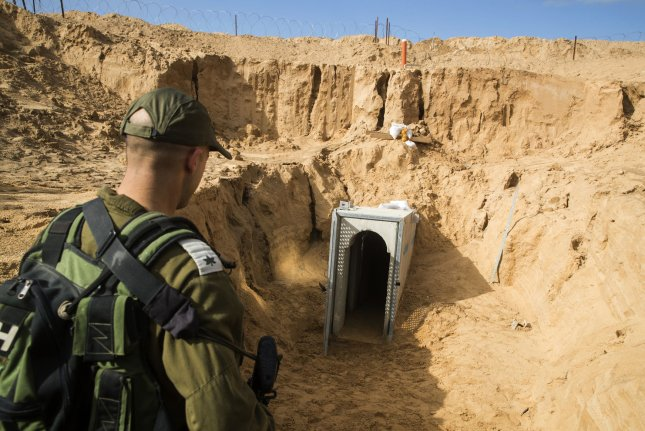 An Israeli army officer walks near the entrance of a tunnel that Israel says was dug by the Islamic Jihad group leading from the Palestinian enclave into Israel, near southern Israeli kibbutz of Kissufim. On Thursday, officials in Israel revealed plans for 40-mile underground wall around Gaza. Photo by Jack Guez/UPIA