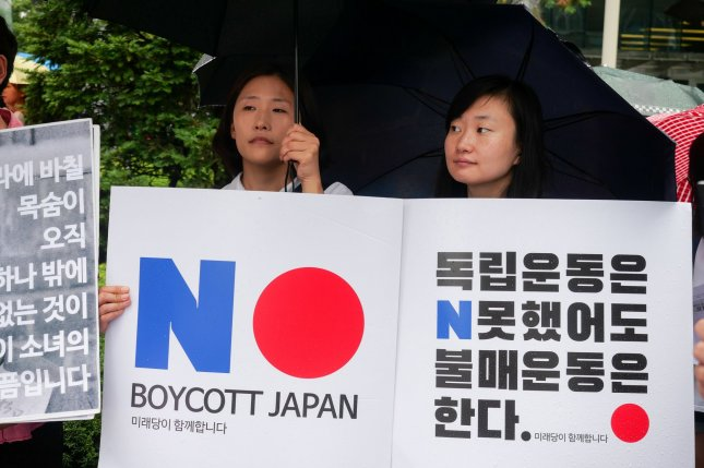 South Korean protesters hold up signs calling for a boycott of Japanese products at the Japanese Embassy in Seoul in July. South Korean authorities said Friday that high-level trade talks have been scheduled between the two countries for December. Photo by Thomas Maresca/UPI