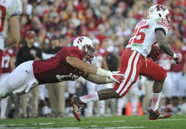 A.J. Tarpley (17) tackles Wisconsin Badgers running back Melvin Gordon in the 2013 Rose Bowl. Tarpley played 13 games in his first NFL season before deciding this week to retire after suffering two concussions. File photo by Lori Shepler/UPI