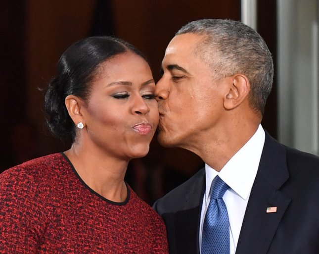President Barack Obama (R) gives Michelle Obama a kiss as they exit the White House before the inauguration of President Donald Trump on January 20. Penguin Random House was the high bidder in the book auction for the U.S. and international rights to publish books by both the former president and first lady. Photo by Kevin Dietsch/UPI