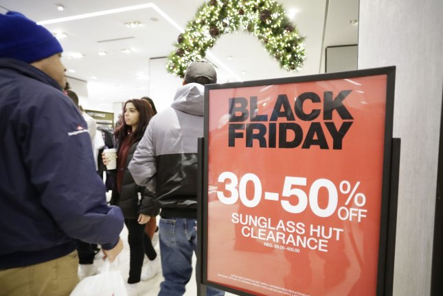 Shoppers holding bags from retail stores walk by discount Black Friday signs in Herald Square on Black Friday in New York City on Friday, November 29, 2019. Online retailers were the big winners Friday, bringing $7.4 billion in sales, but while some traditional retailers have struggled to adapt to customers' shifting preferences, others' stocks have surged this year. Photo by John Angelillo/UPI