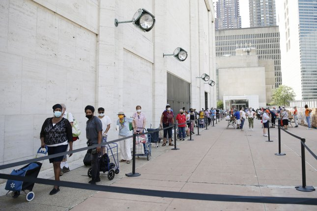 People wear face masks as they wait in line to receive a bag of groceries at a mobile food pantry by Food Bank For New York City. File Photo by John Angelillo/UPI