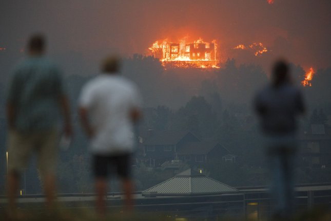 Unidentified residents of Colorado Springs watch as the Waldo Canyon Fire burns a home in the Mountain Shadows neighborhood in Colorado Springs, Colorado on June 26, 2012. The fire exploded Tuesday afternoon after dramatic shifts in the wind and destroyed numerous homes. UPI/Trevor Brown, Jr.