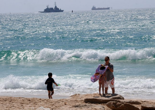 An Israeli family visits the beach while an Israeli naval vessel leaves the Ashdod military port in southern Israel, June 5, 2010. The Israeli navy seized the Rachel Corrie aid ship, carrying 1,200 tonne of aid, and prevented it from reaching Gaza. UPI/Debbie Hill
