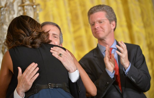 First Lady Michelle Obama hugs Acting VA Secretary Sloan Gibson as Housing and Urban Affairs Secretary Shaun Donovan applauds at an event to announce The Mayors Challenge to End Veteran Homelessness, as part of the Joining Forces initiative, at the White House in Washington, D.C. on June 4, 2014. UPI/Kevin Dietsch.