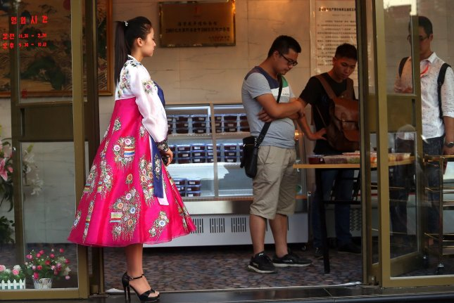 A North Korean hostess watches Chinese people shop for North Korean snacks at a North Korean restaurant in downtown Beijing. Pyongyang has blamed Seoul for the defection of 12 North Korean waitresses. File Photo by Stephen Shaver/UPI