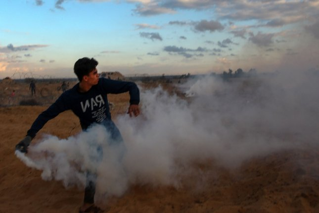A Palestinian protester throws back a tear gas canister fired by Israeli forces during clashes following a demonstration along the border with Israel east of Rafah in the southern Gaza Strip on Friday. Photo by Ismael Mohamad/UPI