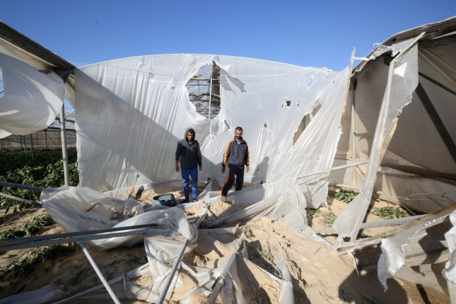 Palestinian men inspect the damage at the site of an Israeli air strike in the southern Gaza town of Khan Younis on Sunday. A rocket was fired at Israel from the Gaza Strip on Saturday, the army said, shortly after warning sirens sounded in the southern Israeli city of Ashkelon. Photo by Ismael Mohamad/UPI