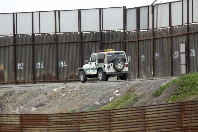 A Border Patrol agent, parked along the levee overlooking the Tijuana River, watches activity along the river basin in San Diego, December 20, 2007. . (UPI Photo/Earl Cryer).