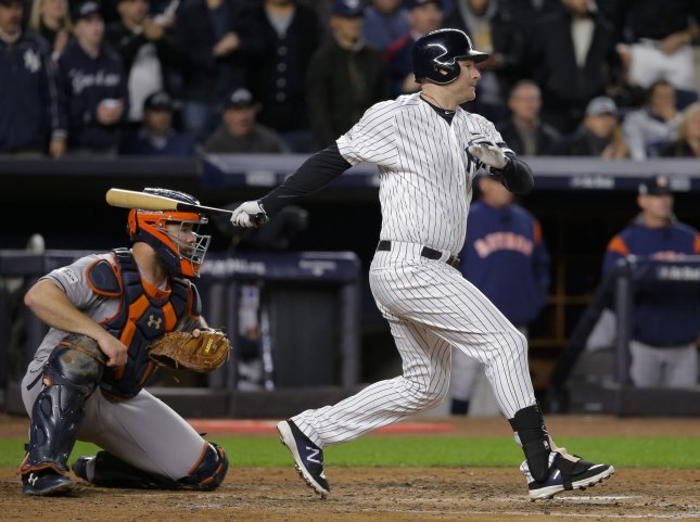 New York Yankees batter Chase Headley hits an RBI single in front of Houston Astros catcher Evan Gattis during the ALCS in October. Photo by Ray Stubblebine/UPI