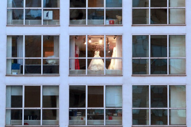 A wedding dress is seen through the window of a retailer. David's Bridal on Monday announced it was seeking Chapter 11 bankruptcy protection. File Photo by Stephen Shaver/UPI