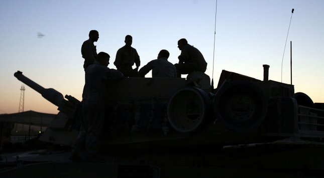 Marine Corps tankers from the Twentynine Palms, Calif.-based Company C, 1st Tank Battalion, rest aboard one of their M1A1 Main Battle Tanks after a 12-hour work day in Iraq's 110-degeree weather in Al Qa'im, Aug. 5, 2006. (Photo/Antonio Rosas/USMC)