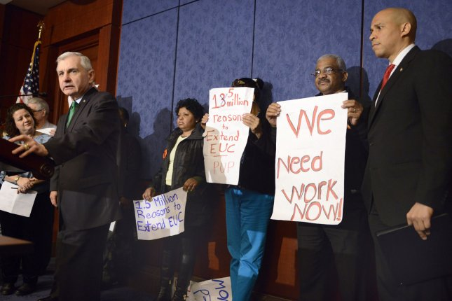 US Sen. Jack Reed (D-RI), (L), makes remarks as Sen. Cory Booker (D-NJ), (R), listens at a press briefing to rally support for Congress to renew unemployment insurance benefits, which earlier failed to pass Republican opposition, at the US Capitol, January 16, 2014, in Washington, DC. Labor leaders hold signs to support jobless Americans. UPI/Mike Theiler