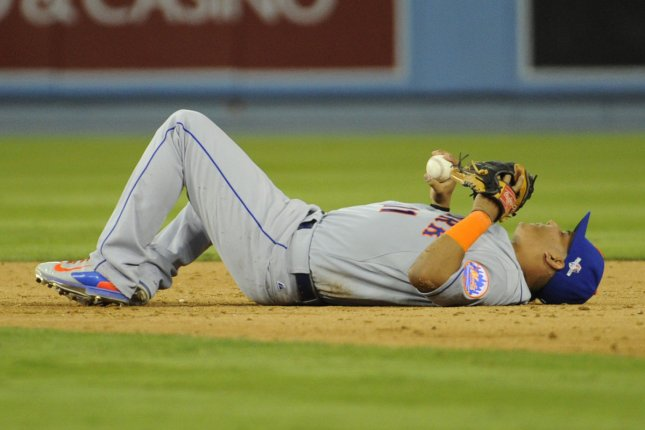 New York Mets' Ruben Tejada lies on the field after a double play with Los Angeles Dodgers Chase Utley, after Tejada fractured his fibula in the seventh inning in game 2 of the National League Division Series against the at Dodger Stadium in Los Angeles on October 10, 2015. The Dodgers won 5-2. Photo by Lori Shepler/UPI