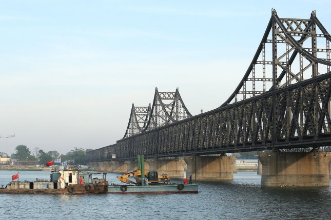A Chinese barge transports a CAT backhoe down the Yalu River past the North Korean city Sinuiju (background), across the Yalu River from Dandong, China's largest border city with North Korea. Discussion of sanctions have been stalled since North Korea conducted its fifth nuclear test in September, but multiple diplomatic sources say progress has been made between U.S. and Chinese envoys. Photo by Stephen Shaver/UPI