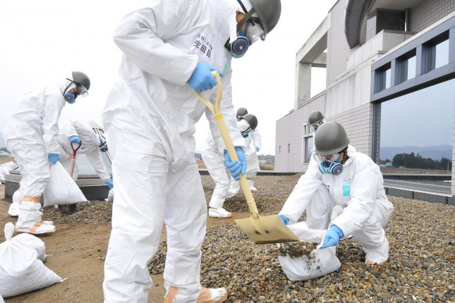 Members of Japan's Ground Self-Defense Force decontaminate an area near the Fukushima Dai-ichi nuclear power plant in Fukushima prefecture, Japan, in December 2011. Japan may be slowly returning to nuclear power after the disaster. File photo by Keizo Mori/UPI