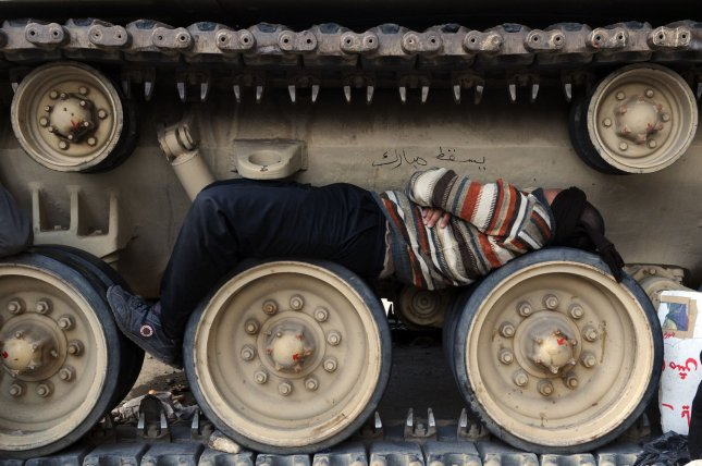 Egyptian anti-government demonstrator lies down on the wheels of a tank at Tahrir Square in Cairo in Egypt on February 6, 2011, on the 13th day of protests calling for the ouster of President Hosni Mubarak. UPI