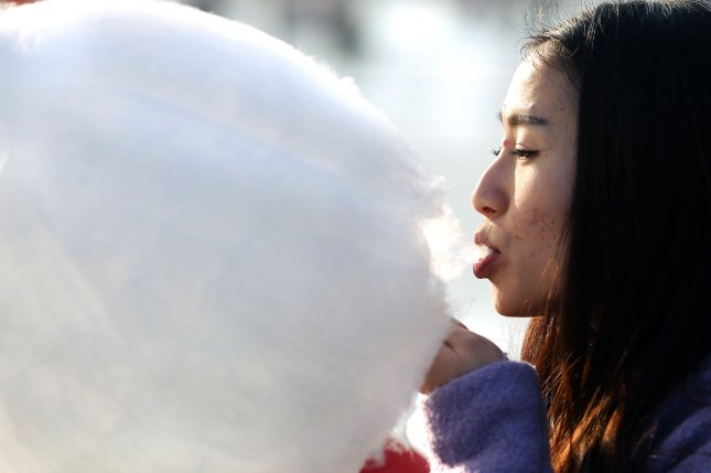 A girl eats cotton candy at a popular tourist area in Beijing. A university in northeastern China has banned students from displays of amorous affection on campus, prompting student ridicule at a time when schools are taking a more interfering role in the personal lives of students. Photo by Stephen Shaver/UPI