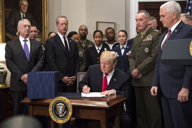 President Donald Trump signs the National Defense Authorization Act for 2018, during a signing ceremony in the Roosevelt Room on Tuesday. Photo by Kevin Dietsch/UPI