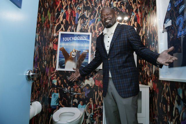 Pro Football Hall of Famer Emmitt Smith smiles as he stands in a football themed Charmin Restroom that is open to the public on December 12, 2017 in Times Square in New York City. File photo by John Angelillo/UPI