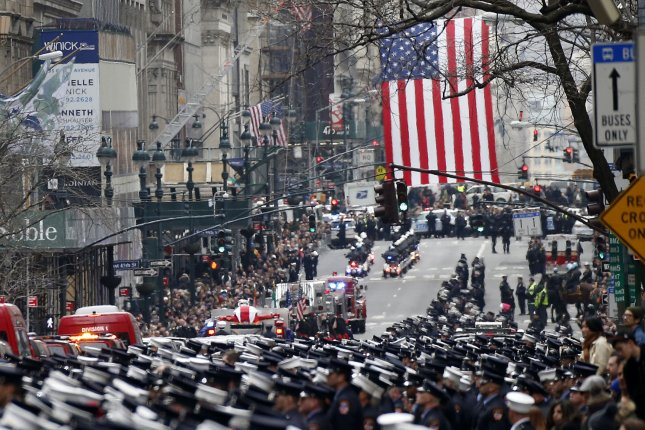 New York firefighters and other officials in uniform stand at attention as the coffin of New York firefighter Michael Davidson travels down Fifth Avenue on a fire truck Tuesday. Photo by John Angelillo/UPI