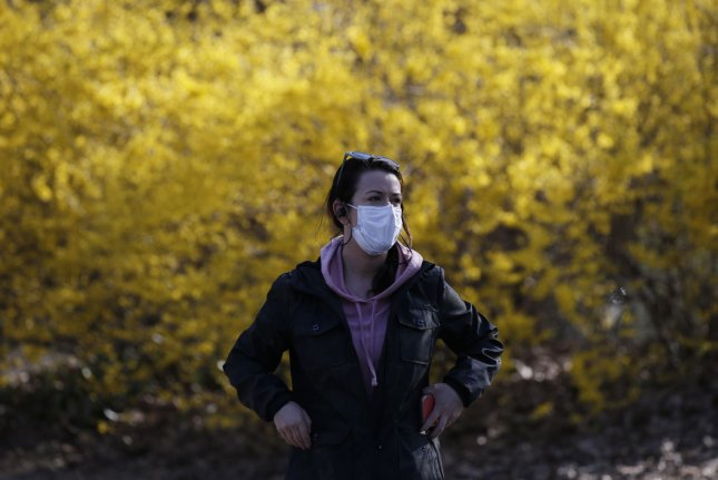 A woman walks in an uncrowded Central Park wearing a protective face mask in New York City on Thursday. Photo by John Angelillo/UPI