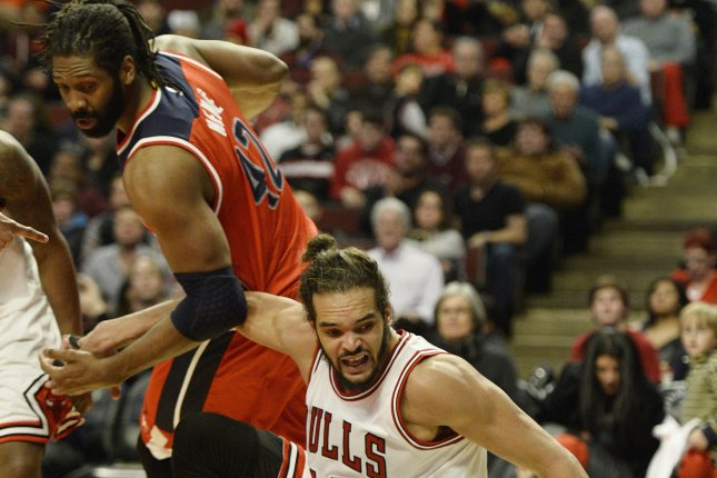 Chicago Bulls center Joakim Noah (R) loses the ball out of bounds as Washington Wizards forward Nene Hilario defends during the fourth quarter at the United Center in Chicago on March 3, 2015. The Bulls defeated the Wizards 97-92. Photo by Brian Kersey/UPI